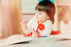 Dibujo de 1 año del bebé con los lápices en casa Foto de archivo