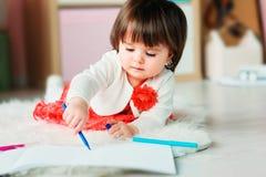 Dibujo de 1 año del bebé con los lápices en casa Imagenes de archivo