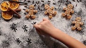 Dibujo de la mano del niño en la harina de las galletas de la Navidad almacen de metraje de vídeo