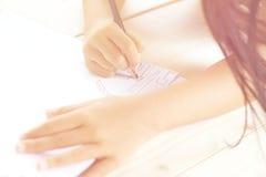 Dibujo de la mano del ` s del niño algo en el Libro Blanco Fotos de archivo