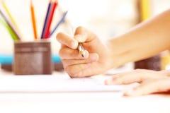 Dibujo de la mano del ` s del niño algo en el Libro Blanco Imagen de archivo libre de regalías