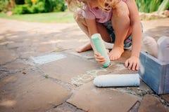 Dibujo de la muchacha del niño con tizas en verano Imagen de archivo libre de regalías