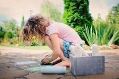 Dibujo de la muchacha del niño con tizas en verano Fotos de archivo libres de regalías