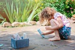 Dibujo de la muchacha del niño con tizas en verano Imagen de archivo