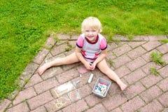 Dibujo de la muchacha del preescolar con tiza al aire libre Fotos de archivo libres de regalías