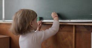 Dibujo de la muchacha en la pizarra usando una tiza en sala de clase Proceso de la educación metrajes
