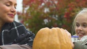 Dibujo de la niña en la calabaza, madre que sonríe, preparación del partido de Halloween almacen de metraje de vídeo
