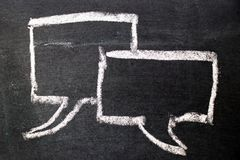 Dibujo de tiza blanco como discurso de la burbuja en fondo negro del tablero imagen de archivo