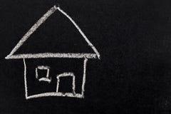 Dibujo de tiza blanco como forma de la casa en tablero negro imágenes de archivo libres de regalías