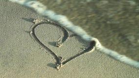 Dibujo de un corazón en la arena y el lavado por la ola oceánica metrajes
