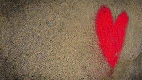 Dibujo de un corazón rojo en una pared sucia vieja fotos de archivo