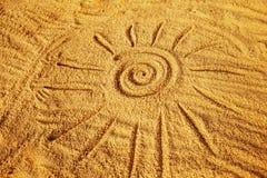 Dibujo de un símbolo del sol en la arena de oro en la costa Foto de archivo libre de regalías