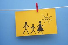 Dibujo de una familia en trozo de papel amarillo Foto de archivo libre de regalías