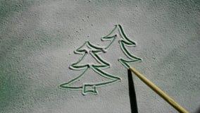 Dibujo de una tarjeta de Navidad en la imitación de la nieve con una manija de madera