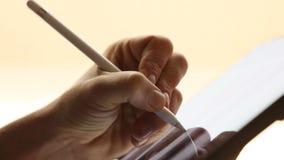 Dibujo del diseñador de la mano en la tableta digital con la pluma de la aguja almacen de video
