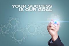 Dibujo del hombre de negocios en la pantalla virtual Su éxito es nuestro concepto de la meta foto de archivo