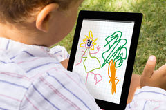 Dibujo del muchacho con la tableta Imagen de archivo