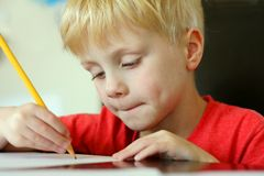 Dibujo del niño joven en el papel con el lápiz Imagen de archivo libre de regalías