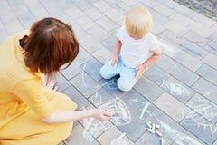 Dibujo del niño pequeño con tizas en el asfalto Imagenes de archivo