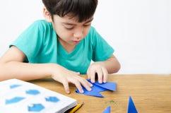 Dibujo del niño pequeño en la papiroflexia de papel del arte Foto de archivo