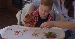 Dibujo del padre con el niño que usa el tiempo coloreado del gasto de la pintura del finger junto almacen de metraje de vídeo