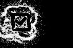 Dibujo del símbolo de la marca de comprobación por el finger en el polvo blanco de la sal en fondo negro imágenes de archivo libres de regalías