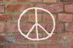 Dibujo del signo de la paz en la pared de ladrillo roja Imagenes de archivo