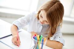 Dibujo feliz de la muchacha con el rotulador en cuaderno Imagen de archivo