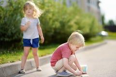 Dibujo feliz del niño pequeño y de la muchacha con tiza coloreada en el asfalto Fotos de archivo libres de regalías