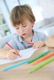 Dibujo joven feliz del muchacho en un papel Imagen de archivo libre de regalías