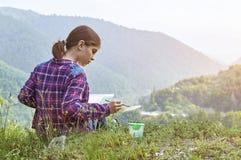 Dibujo lindo de la muchacha del adolescente con la brocha en lugar hermoso Imagen de archivo libre de regalías