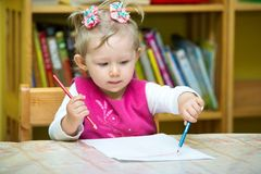 Dibujo lindo de la muchacha del niño con los lápices coloridos en preescolar en la tabla en guardería fotografía de archivo libre de regalías