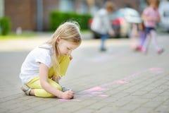 Dibujo lindo de la niña con tizas coloridas en una acera Actividad del verano para los pequeños niños Fotos de archivo