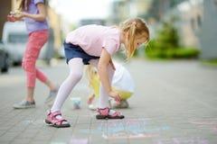 Dibujo lindo de la niña con tizas coloridas en una acera Actividad del verano para los pequeños niños Fotografía de archivo