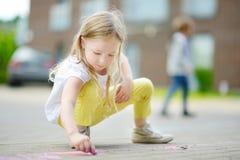 Dibujo lindo de la niña con tizas coloridas en una acera Actividad del verano para los pequeños niños Imágenes de archivo libres de regalías