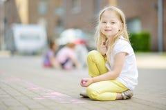 Dibujo lindo de la niña con tizas coloridas en una acera Actividad del verano para los pequeños niños Imagenes de archivo