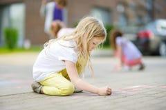 Dibujo lindo de la niña con tizas coloridas en una acera Actividad del verano para los pequeños niños Foto de archivo libre de regalías
