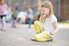 Dibujo lindo de la niña con tizas coloridas en una acera Actividad del verano para los pequeños niños Imagen de archivo libre de regalías