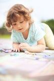 Dibujo lindo de la niña pequeña con el pedazo de tiza del color Imagenes de archivo