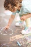Dibujo lindo de la niña pequeña con el pedazo de tiza del color Fotografía de archivo