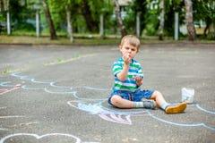 Dibujo lindo del muchacho y de la muchacha con tiza en la acera en el parque Imagen de archivo
