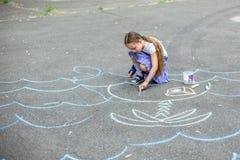 Dibujo lindo del muchacho y de la muchacha con tiza en la acera en el parque Fotos de archivo