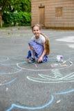 Dibujo lindo del muchacho y de la muchacha con tiza en la acera en el parque Fotografía de archivo libre de regalías