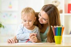 Dibujo lindo del niño con ayuda de la madre Imagen de archivo