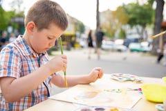 Dibujo lindo del niño pequeño con las pinturas coloridas en parque de la caída Pintura creativa del niño en la naturaleza Al aire imagen de archivo