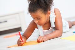 Dibujo preescolar lindo de la muchacha del niño en el piso Imagen de archivo