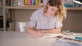 Dibujo que bosqueja del artista de la mujer joven que crea arte metrajes