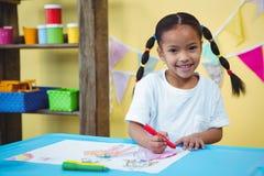 Dibujo sonriente de la muchacha en su libro de colorante Imagen de archivo