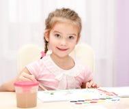 Dibujo sonriente lindo de la niña con la pintura y la brocha Imagen de archivo libre de regalías