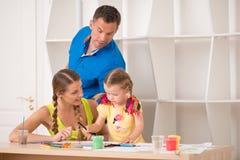 Dibujo y pintura felices preciosos de la familia en casa Foto de archivo